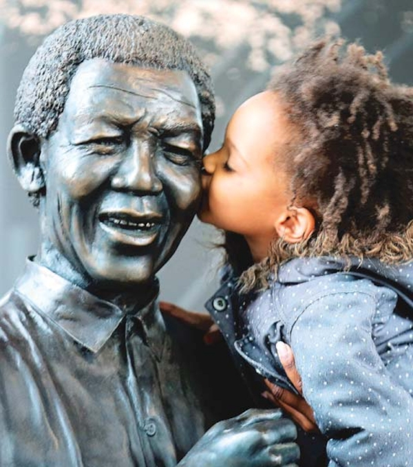 Girl kisses Mandela statue