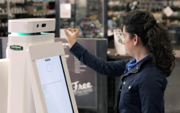 Woman interacting with OSHbot, Lowe's robot